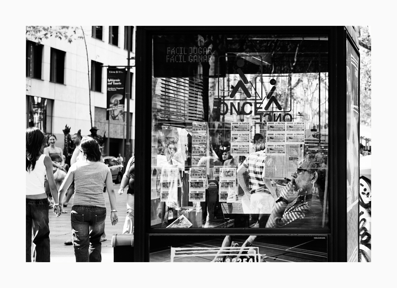 Fine art image of a man smoking in his lottery stand at La Rambla, Barcelona, Spain.