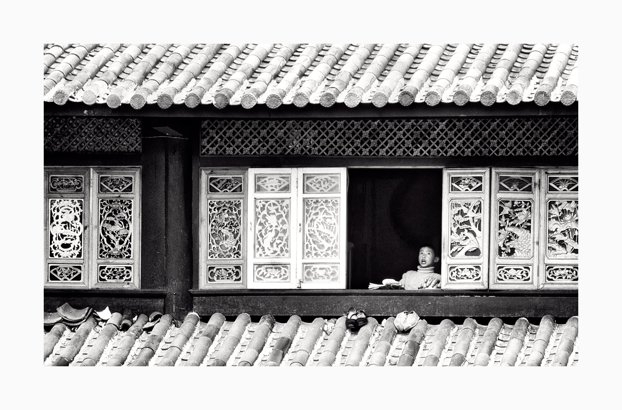 Black and white image of a boy breaking into song at a window in Lijiang, China