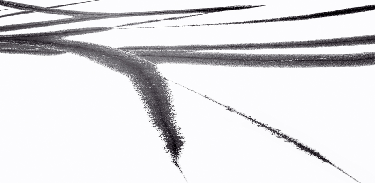 Fine art black and white image of calligraphy-like brush strokes on a frozen lake.