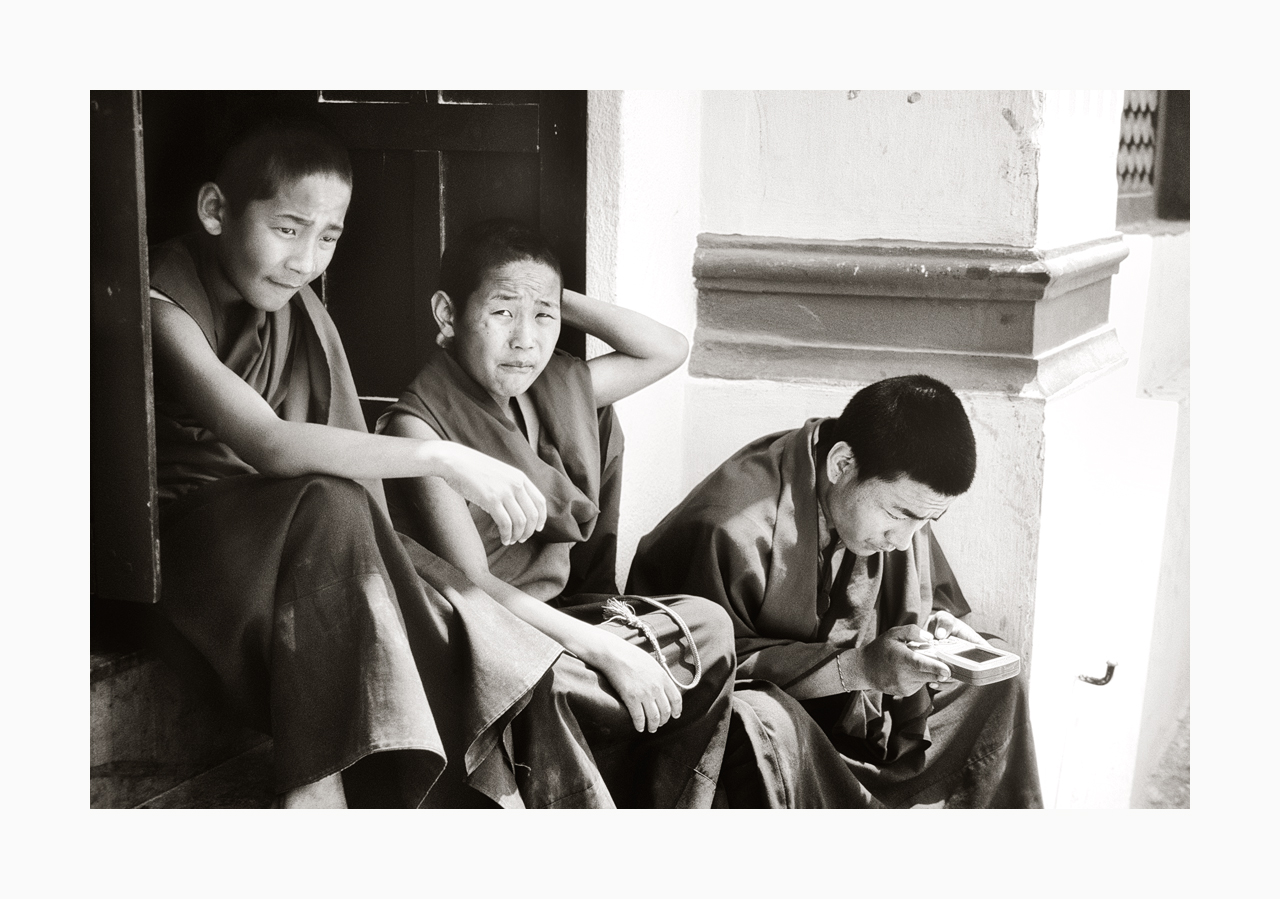 Fine art black and white image of monks playing with a Gameboy in the '90s, Nepal.