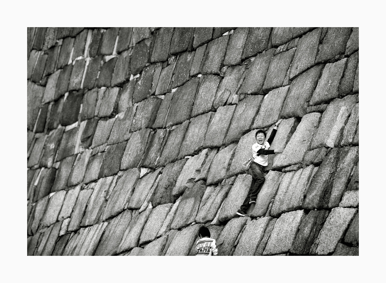 Fine art black and white image of kids climbing Osaka Castle Wall, Japan.