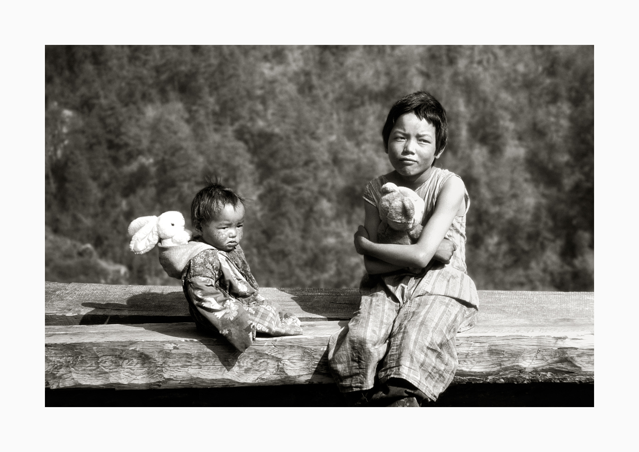 Fine art image of a young girl and infant with pristine stuffed toys, from '90s, Nepal