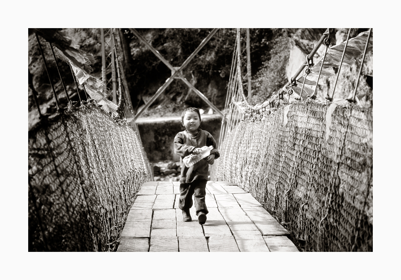 Fine art image of a boy with a plastic bottle crossing a bridge from the '90s, Nepal.
