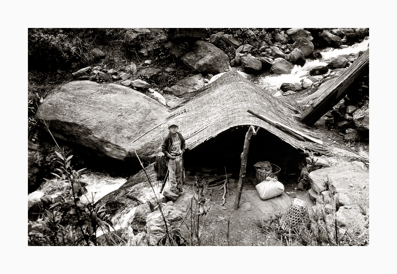Fine art image of a boy on duty at a hut beside a river, from '90s, Nepal.