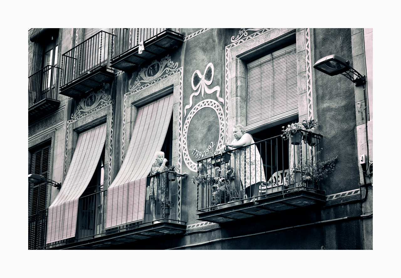 Fine art image of elderly neighbours facing each other on their balconies in Barcelona.