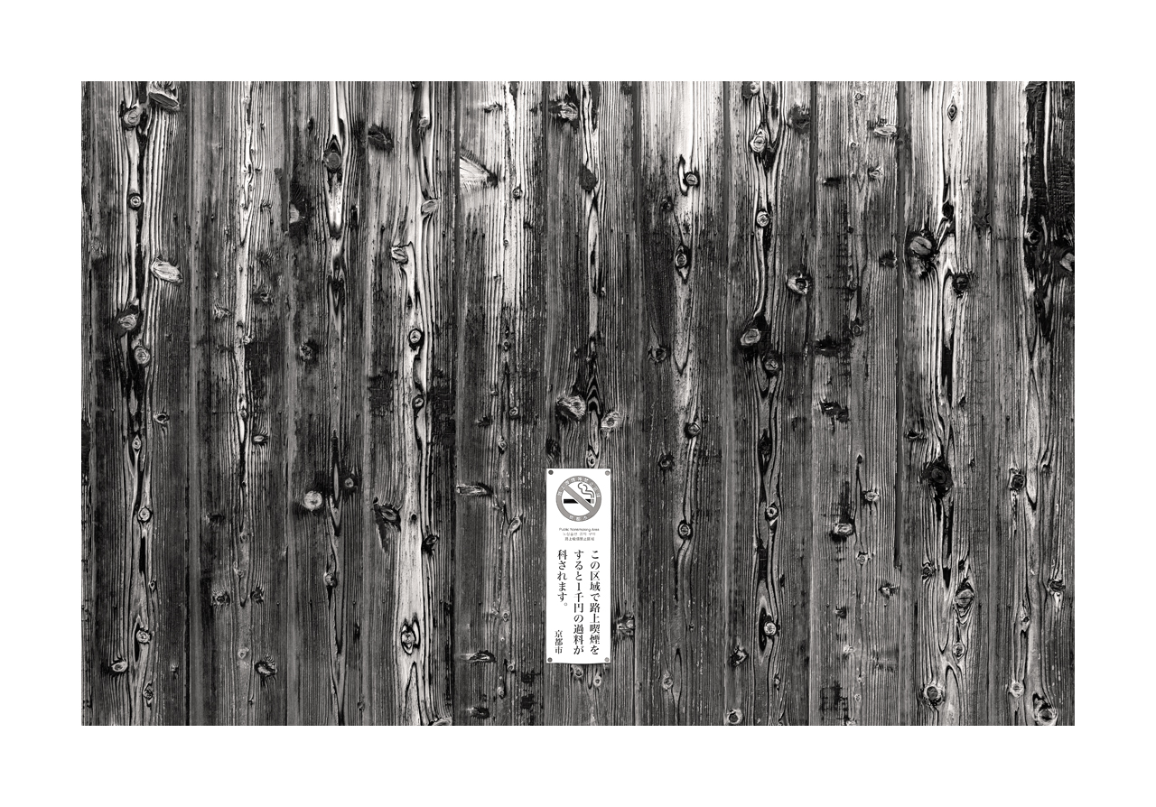 Fine art black and white image of a wooden fence with pronounced grain and no smoking warning sign.