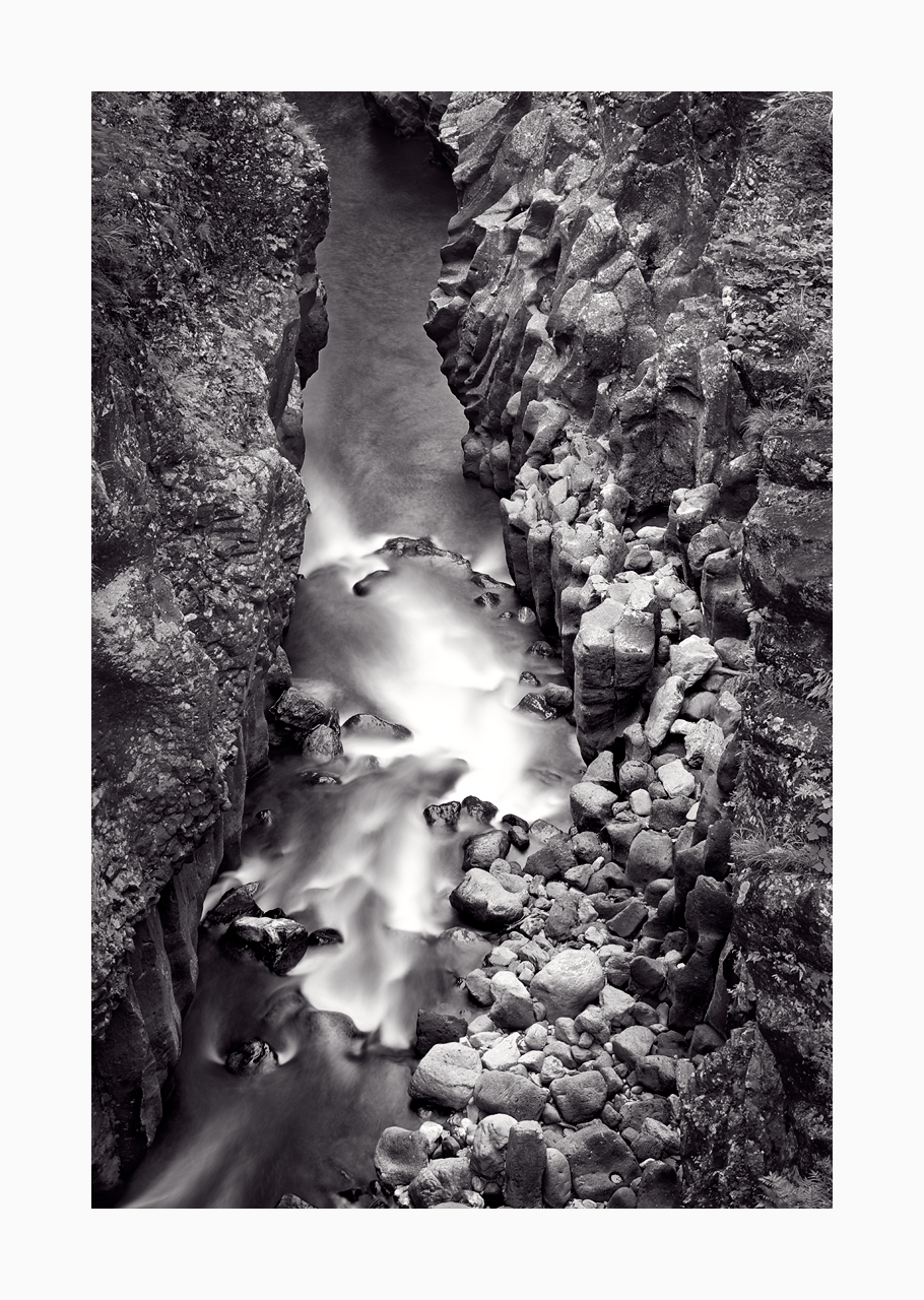 Fine art black and white image of basalt column walls and water flow of Takachiho Gorge, Japan.